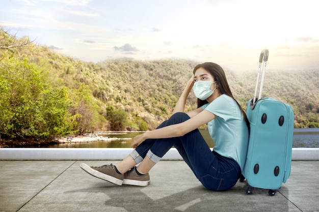 Asiatische frau mit einer gesichtsmaske, die mit einem koffer auf der straße sitzt. reisen in der neuen normalität
