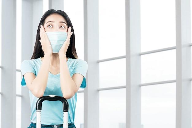 Asiatische frau mit einer gesichtsmaske mit einem koffer auf dem krankenhaus. ärztliche untersuchung vor reiseantritt