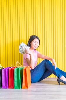 Asiatische frau mit einkaufstüten, die notizen halten
