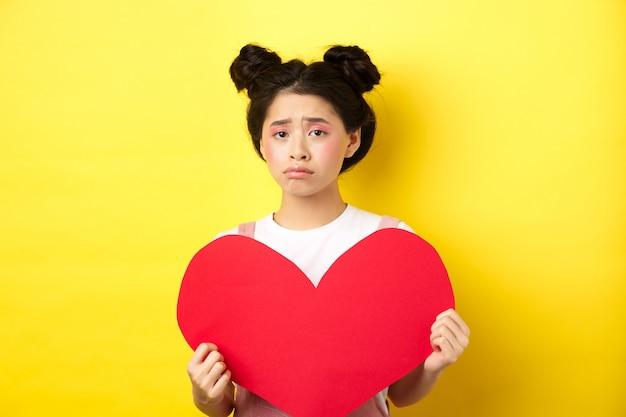 Asiatische frau mit gebrochenem herzen, die großen roten herzausschnitt zeigt und traurig aussieht, sich am tag des liebhabers einsam fühlt und valentinskarte an der kamera, gelben hintergrund zeigt.