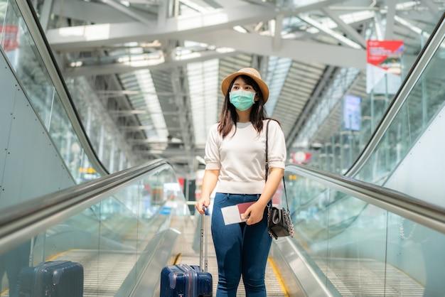 Asiatische frau mit gepäck, das gesichtsmaske trägt