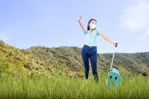 Asiatische frau mit gesichtsmaske, die mit einem koffer auf dem feld steht. reisen in der neuen normalität