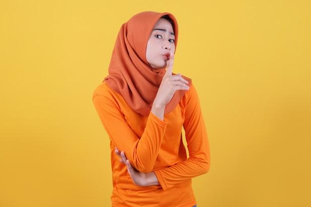 Asiatische frau mit hijab besorgt, nervös, panisch, aggressiv, wütende frau zeigt eine geste des schweigens und hält einen zeigefinger in der nähe des mundes