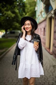 Asiatische frau mit hut und sonnenbrille handy-anruf sprechen stadtstraße
