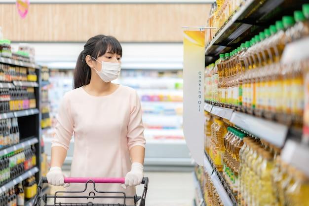 Asiatische frau mit hygienemaske und gummihandschuh mit einkaufswagen im lebensmittelgeschäft und auf der suche nach einer speiseölflasche, die während des ausbruchs der covid-19 zur vorbereitung auf eine pandemiequarantäne gekauft werden kann