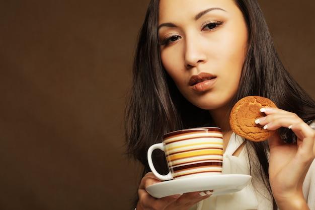 Asiatische frau mit kaffee und keksen.