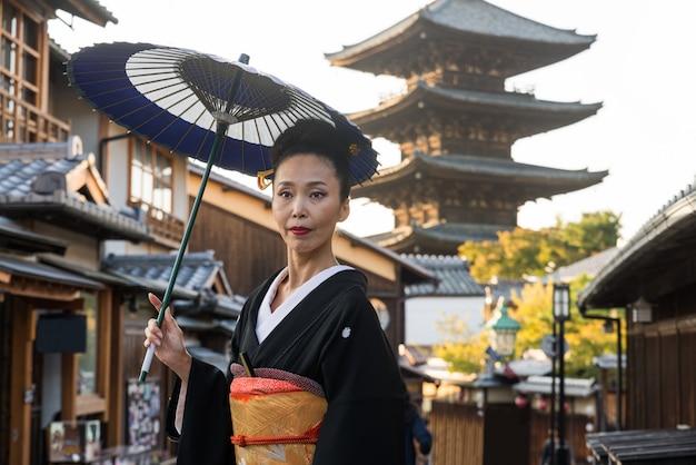 Asiatische frau mit kimono, die an yasaka-pagode in kyoto geht