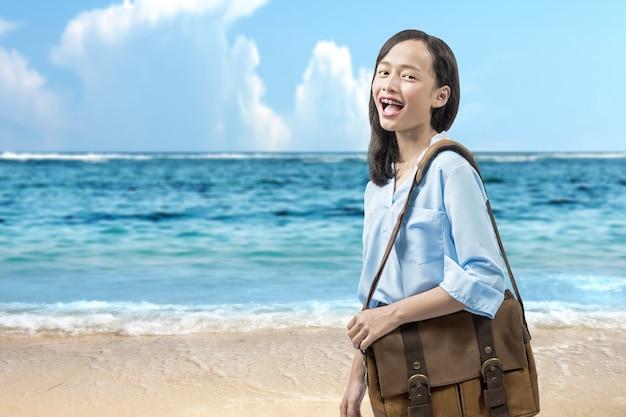 Asiatische frau mit koffer, die am strand mit blauem himmelshintergrund reist