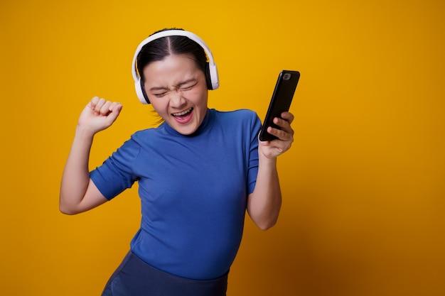 Asiatische frau mit kopfhörern, die musik vom smartphone auf gelb hören.