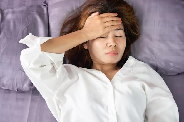 Asiatische frau mit kopfschmerzen, migräne oder schwindel im bett