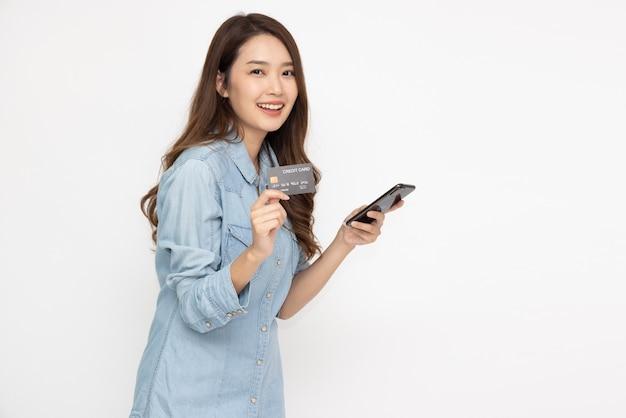 Asiatische frau mit kreditkarte über online-anwendung im smartphone isoliert auf weißem hintergrund