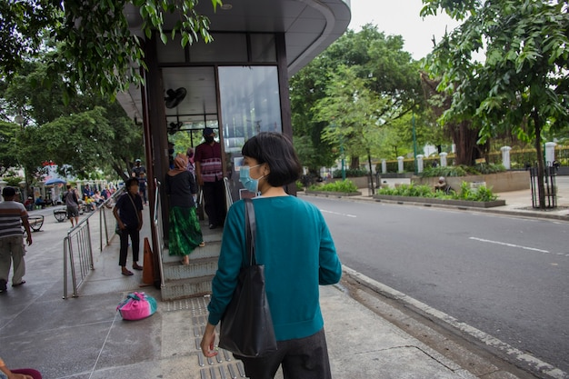 Asiatische frau mit medizinischer maske, die auf den bus am bahnhof des öffentlichen verkehrs wartet