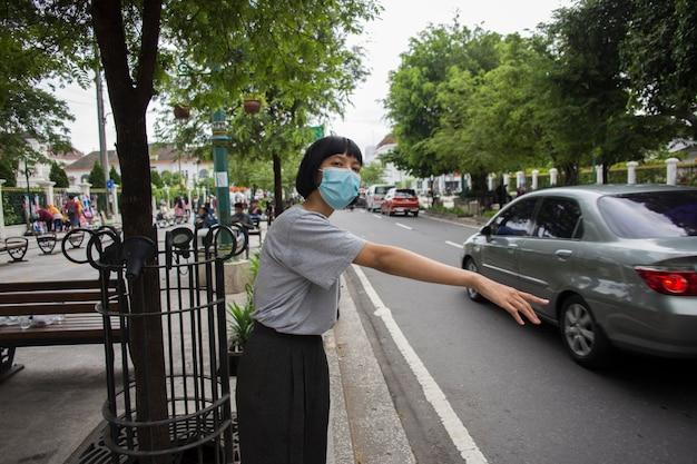 Asiatische frau mit medizinischer maske, die draußen auf öffentliche verkehrsmittel wartet