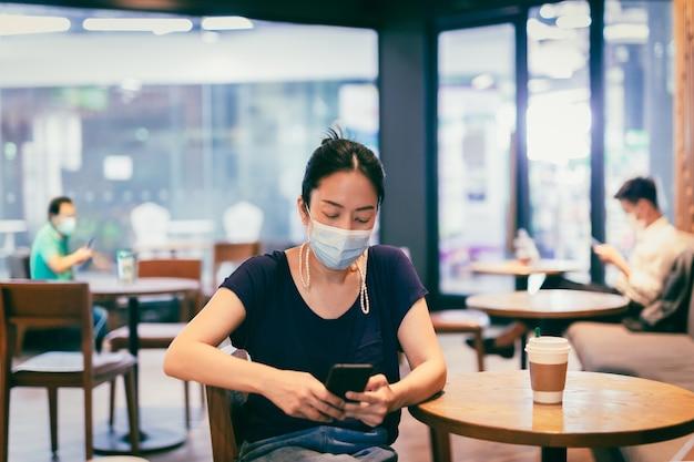 Asiatische frau mit medizinischer maske mit handy am tisch im café sitzend