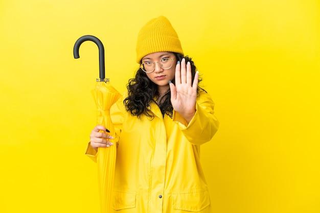 Asiatische frau mit regenfestem mantel und regenschirm isoliert auf gelbem hintergrund, die stopp-geste macht