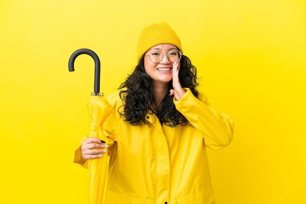 Asiatische frau mit regenfestem mantel und regenschirm isoliert auf gelbem hintergrund schreiend mit weit geöffnetem mund