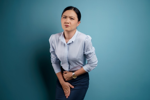 Asiatische frau mit schmerzhaften händchenhalten, die ihren schrittunterbauch drücken