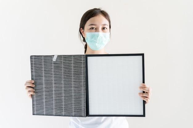 Asiatische frau mit schützender hygienegesichtsmaske, die einen hepa-luftreinigerfilter ändert