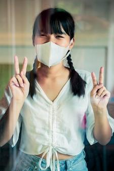 Asiatische frau mit schutzmaske, die hinter dem hausspiegeltürschild victory hand steht