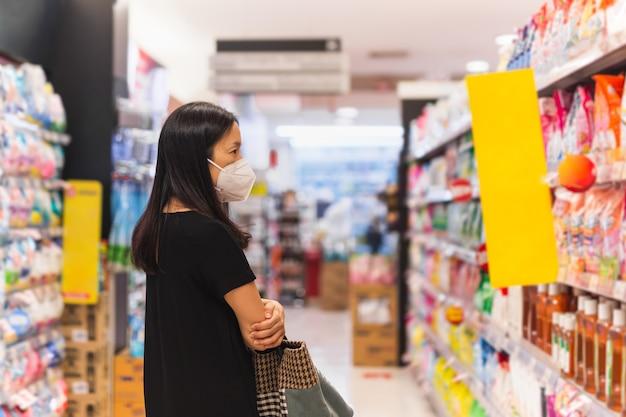 Asiatische frau mit schutzmaske, die während der coronavirus-pandemie lebensmittel im supermarkt auswählt