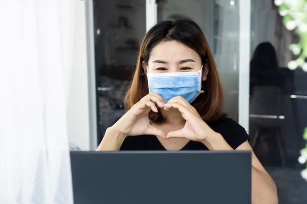 Asiatische frau mit schutzmaske in liebesvideoanruf mit freund