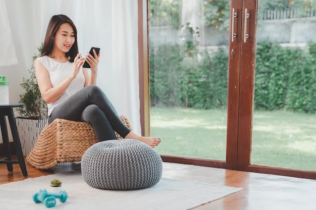 Asiatische frau mit smartphone, um einen online-fitnesskurs vor dem training zu hause im wohnzimmer zu finden workout