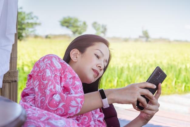 Asiatische frau mit smartphone, während sie auf einem kissen mit blick auf die natur liegt