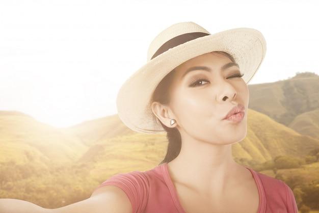 Asiatische frau mit strohhut macht selfie mit ihrem smartphone