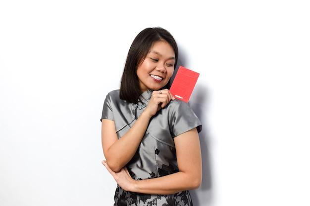 Asiatische frau mit traditionellem cheongsam zeigt und hält roten umschlag angpau