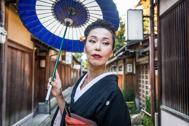 Asiatische frau mit yukata, die in kyoto, japan geht