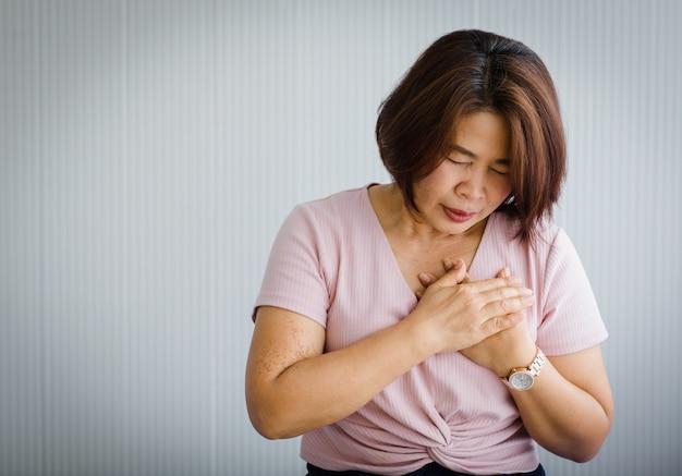 Asiatische frau mittleren alters, die auf dem bett sitzt und an einem plötzlichen herzinfarkt leidet und die brust hält. konzept der notfallversorgung und von herz-lungen-wiederbelebung, herzproblemen betroffen.