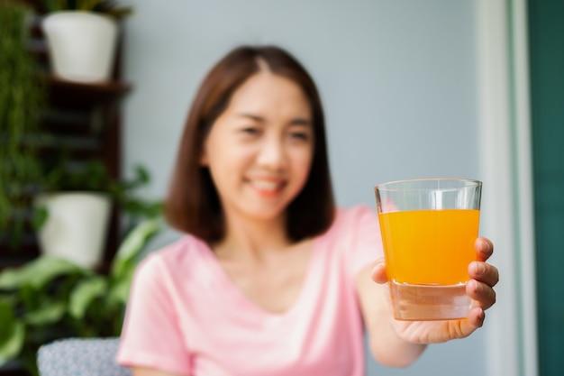 Asiatische frau mittleren alters, die ein buch liest und orangensaftglas im haus hält. konzept der gesundheitsversorgung und essen für gesund