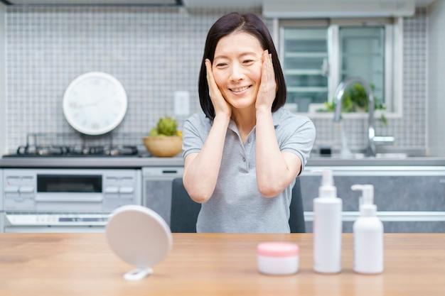 Asiatische frau mittleren alters, die hautzustand zu hause prüft