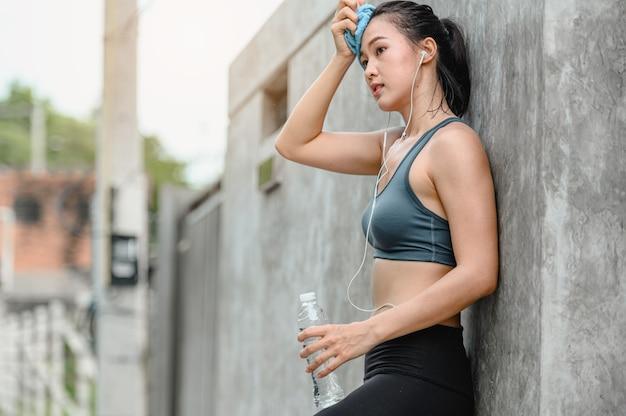 Asiatische frau müde sportübungen.sie mit handtuch wischt schweiß von ihrem gesicht.sie steht im freien. fitness, training, fitnesstraining, lebensstil und gesundes konzept.