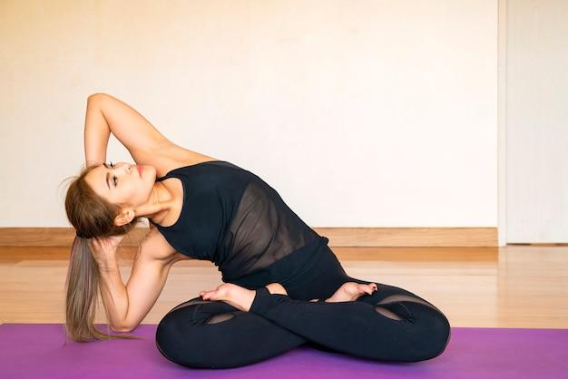 Asiatische frau praktizieren yoga-workout-übung auf yogamatte in ihrem wohnzimmer zu hause. gesunder lebensstil, neues normales oder hausquarantänekonzept