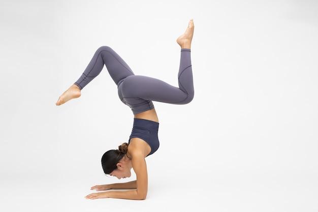 Asiatische frau praktiziert inversion balancing yoga-pose handstand isoliert auf weißem hintergrund