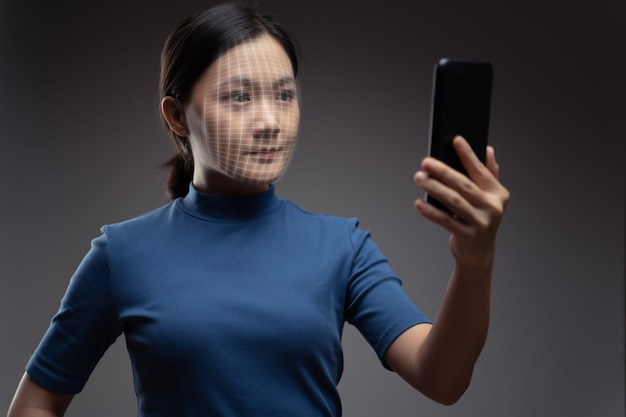 Asiatische frau scannt gesicht durch smartphone unter verwendung des gesichtserkennungssystems. isoliert