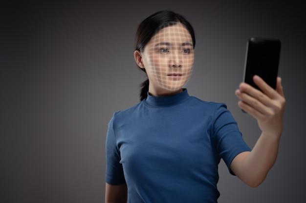 Asiatische frau scannt gesicht durch smartphone unter verwendung des gesichtserkennungssystems