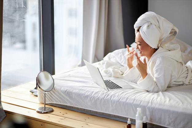 Asiatische frau schaut auf bildschirm des laptops, der spricht, lächelt, online-gespräch mit jemandem hat, zu hause auf dem bett
