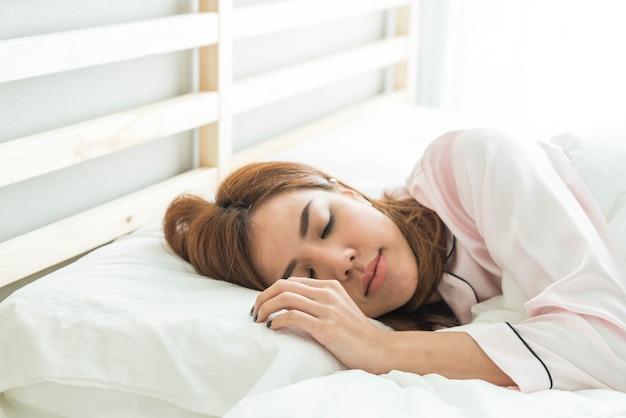 Asiatische frau schläft auf dem bett