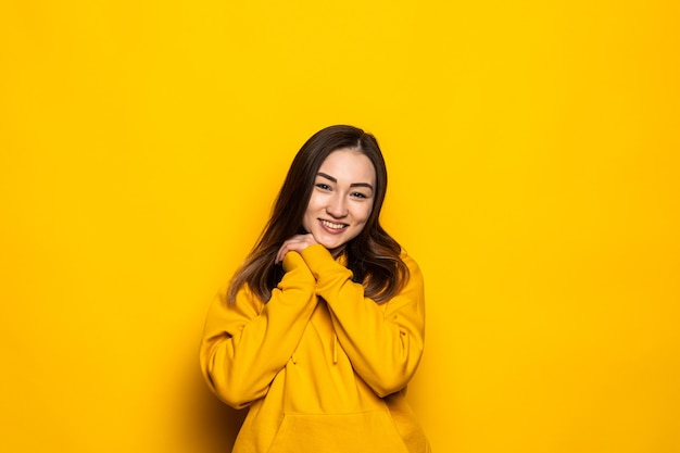 Asiatische frau schüchtern isoliert auf gelber wand im studio