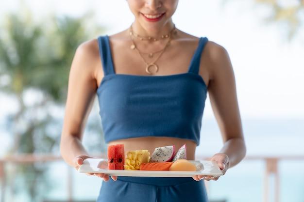 Asiatische frau serviert obstteller im hotelgarten.