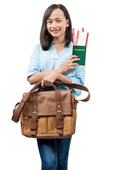 Asiatische frau stehend mit einer aktentasche, die ticket und pass hält