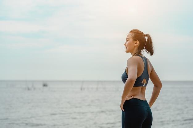 Asiatische frau steht, um am strand natürliche luft zu atmen gesunde fitness- und lifestyle-übungen