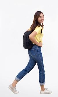 Asiatische frau teenager mit schule bagwalking auf weißem hintergrund mit freizeitkleid