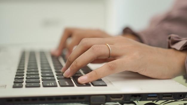Asiatische frau tippt auf ihrem laptop
