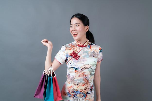 Asiatische frau trägt chinesisches traditionelles kleid mit der hand, die einkaufstasche auf grauem hintergrund hält