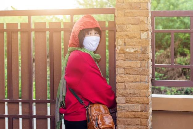 Asiatische frau trägt eine chirurgische maske, bevor sie das haus verlässt, um die infektion durch covid-19 zu reduzieren