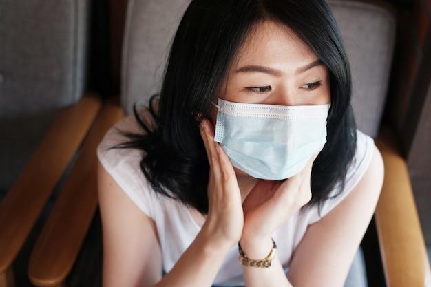 Asiatische frau trägt eine maske zur vorbeugung von covid19 und infektions-corona-virus