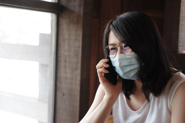 Asiatische frau trägt eine maske zur vorbeugung von covid19 und ruft das smartphone an